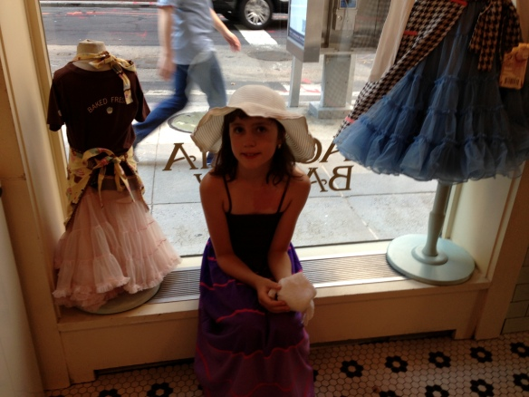 Emilie with her new dress in the window of Magnolia Bakery